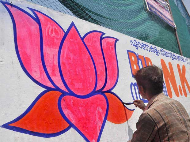 A worker draws BJP party symbol 'Lotus' on a wall in Kochi
