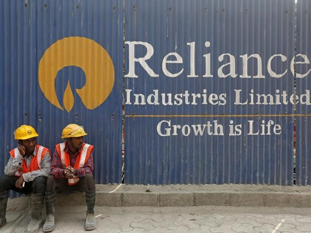 Labourers rest in front of an advertisement of Reliance Industries Limited in Mumbai. Photo: Reuters