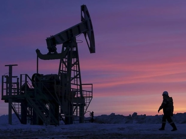 A worker walks past a pump jack on an oil field in Russia  Reuters