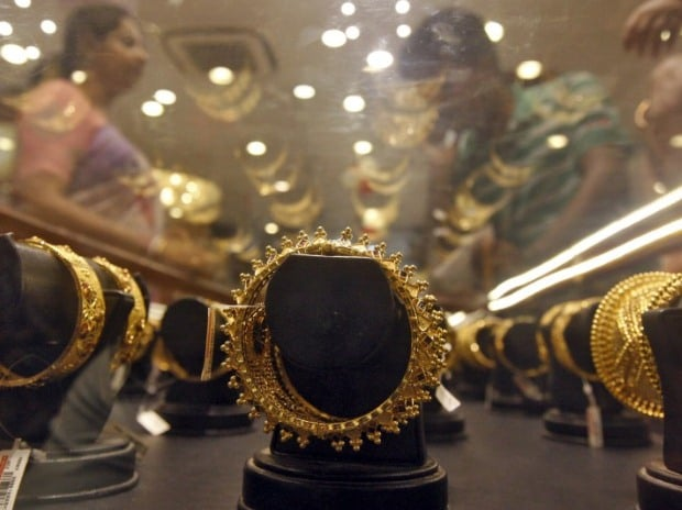 Gold bracelets are on display as a woman (L) makes choices at a jewellery showroom on the occasion of Akshaya Tritiya, a major gold buying festival, in Kolkata