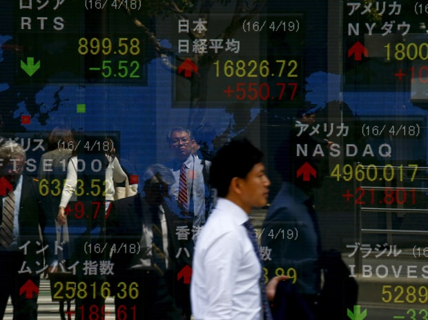A man walks past a display of the Nikkei average and other market indices outside a brokerage in Tokyo. Photo: Reuters