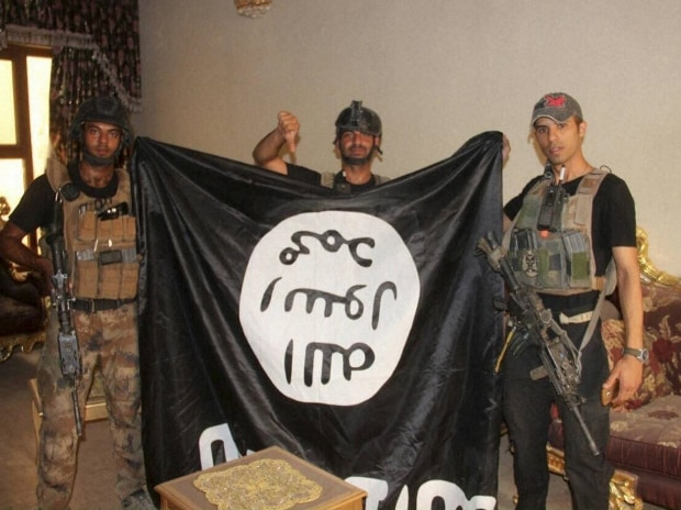 File photo. Iraqi soldiers pose with an Islamic State militant flag in Fallujah, Iraq after forces re-took the city center after two years of IS control