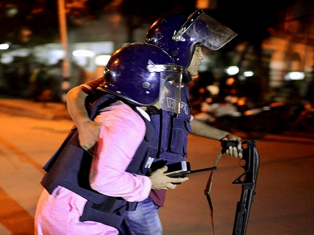 An unidentified security personnel is taken for medical attention after a group of gunmen attacked a restaurant popular with foreigners in a diplomatic zone of the Bangladeshi capital Dhaka.