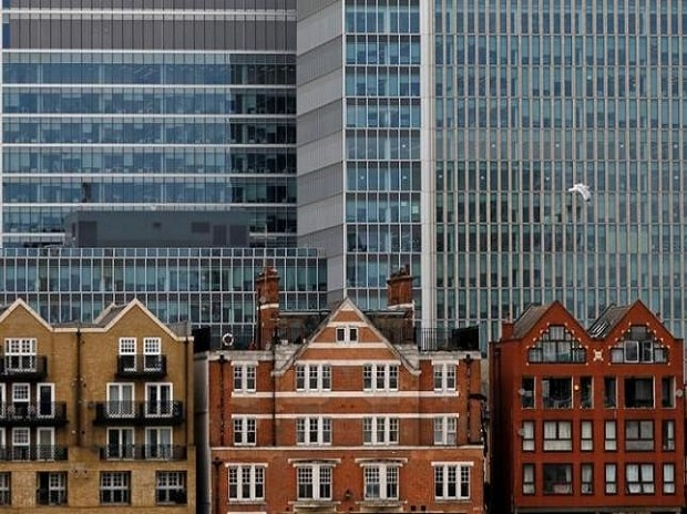Apartment buildings are backdropped by skyscrapers of banks at Canary Wharf in London. Photo:Reuters