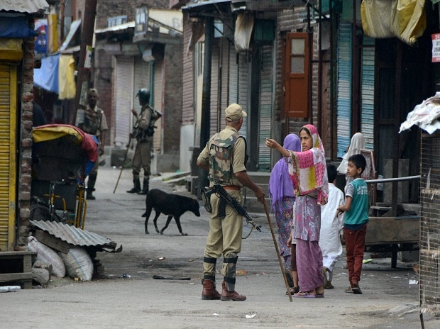 A woman seeks permission from a security man during curfew and strike in Srinagar Photo: PTI