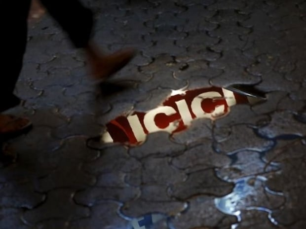 ICICI bank signboard is reflected in a puddle on ...