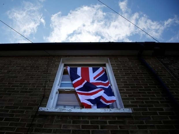 A British flag flutters in front of a window in London