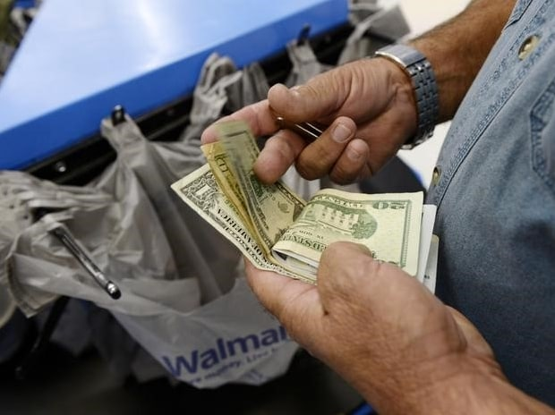 A customer counts his cash at the checkout lane of a Walmart store in the Porter Ranch section of Los Angeles  Reuters