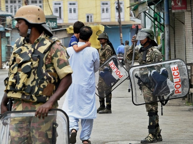 A man with his child walks past Security jawans during curfew and strike in Srinagar
