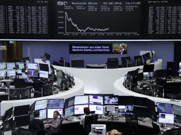 Traders work at their desks in front of the German share price index