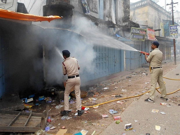 Fire fighters dousing burning shops after clashes  between two communities in Chhapra, Saran district of Bihar.