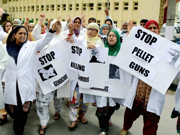 Nurses and paramedics hold placards and shout slogans during a protest rally against the killing of 55 civilians and use of pellet guns by forces, outside SMHS Hospital in Srinagar