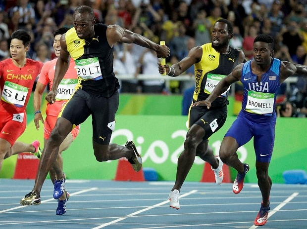 Jamaica's Nickel Ashmeade, second right, passes the baton to Usain Bolt in the men's 4 x 100-meter relay final