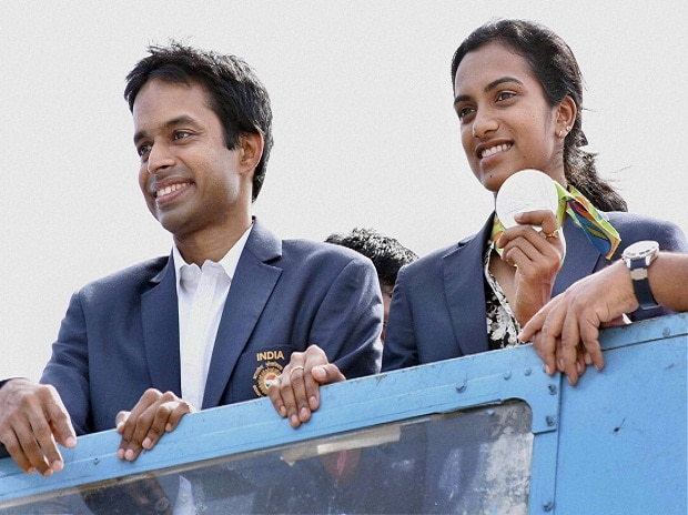 Olympic Silver Medalist P V Sindhu with her Coach Pullela Gopichand flaunts her medal after her arrival at Rajiv Gandhi International Airport in Hyderabad.