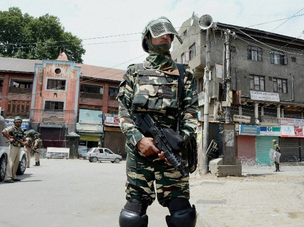 A security person stands guard in a street during the 45th day of curfew in Srinagar