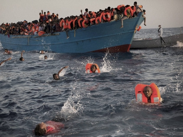 Migrants, most of them from Eritrea, jump into the water from a crowded wooden boat as they are helped by members of an NGO during a rescue operation at the Mediterranean sea