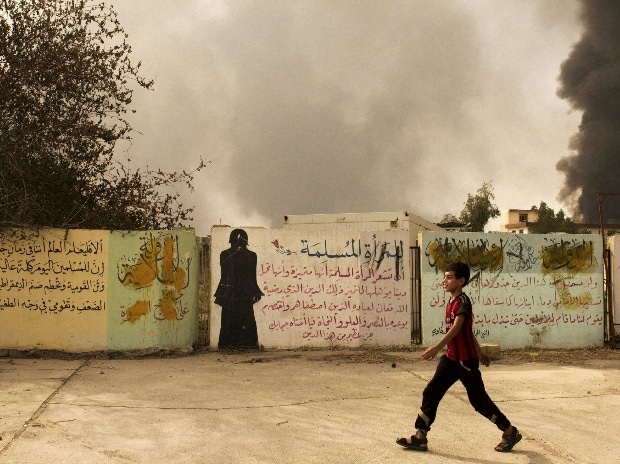 A young boy walks past partially defaced Islamic State group instructions for muslim women and a written warning to violators of the militant, Iraq