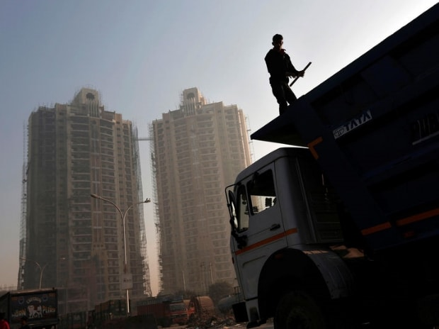 A labourer stands on a truck carrying construction materials at a construction site of residential buildings  Reuters