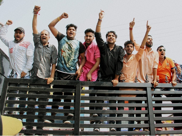 Activists of Bajrang Dal climb at the main gate of the Government Circuit House during a protest against the All Party Delegation for appeasing separatist elements in the Kashmir valley