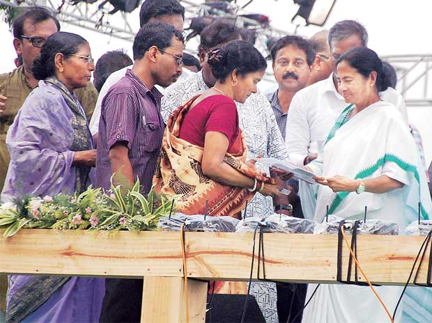 West Bengal Chief Minister Mamata Banerjee hands over the title deed for the land acquired for Tata Motors to a farmer in Singur