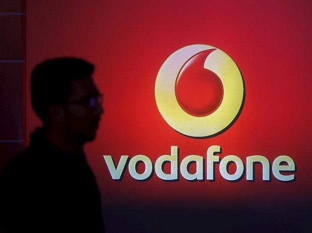 A man casts a silhouette onto an electronic screen displaying a Vodafone logo, in Mumbai. Photo: Reuters