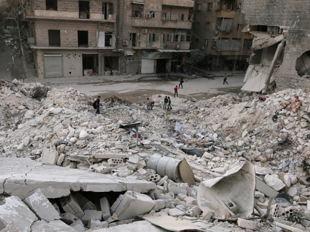 People walk on the rubble of damaged buildings in the rebel held area of al-Kalaseh neighbourhood of Aleppo, Syria. Photo: Reuters