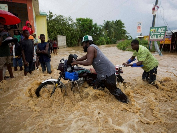 Two men push a motorbike through a street flooded by a nearby river that overflowed from heavy rains caused by Hurricane Matthew, in Leogane, Haiti. Photo: PTI