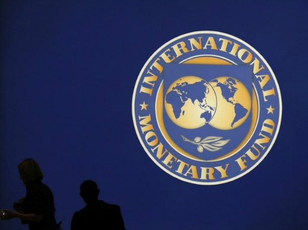 Visitors are silhouetted against the logo of the International Monetary Fund at the main venue for the IMF and World Bank annual meeting in Tokyo. (Photo: Reuters)