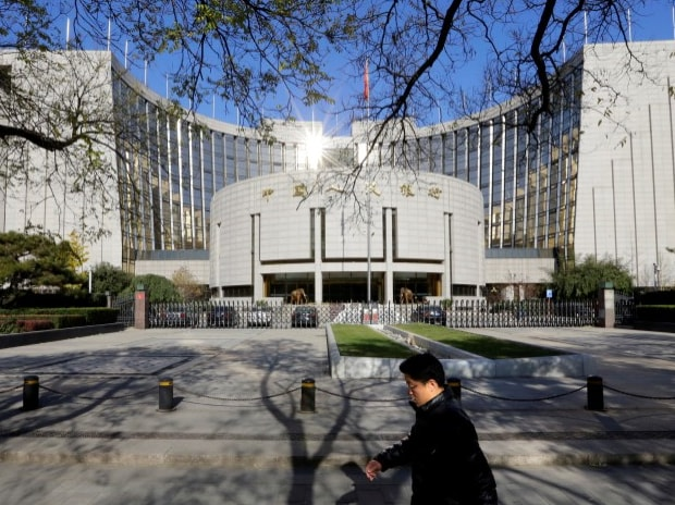 A man walks past the headquarters of the PBOC in Beijing