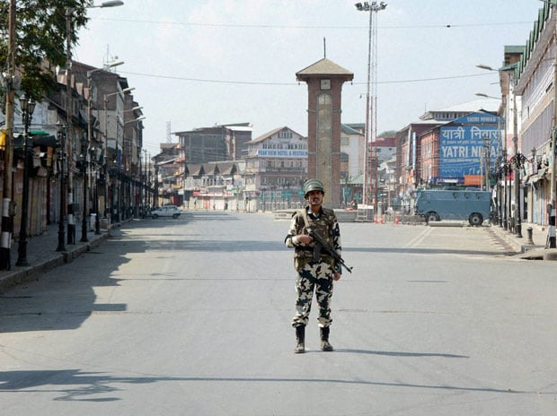 A security jawan patrolling on a deserted street during curfew in Srinagar. (Photo: PTI)