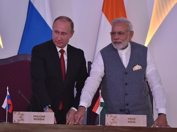 Russian President Vladimir Putin (L) shakes handS with India's Prime Minister Narendra Modi during a photo opportunity ahead of India-Russia Annual Summit in Benaulim, in Goa