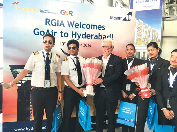 GoAir CEO Wolfgang Prock-Schauer with airline crew at the launch of its maiden flight in Hyderabad