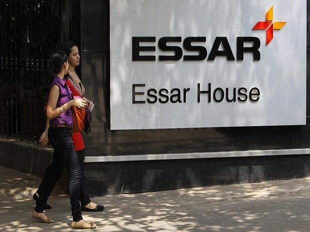 Employees walk past an Essar Group logo outside ...