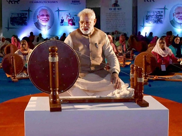 Prime Minister Narendra Modi works at a charkha at a ceremony to distribute charkhas to women before the National MSME Awards at Punjab Agricultural University in Ludhiana.Photo:PTI