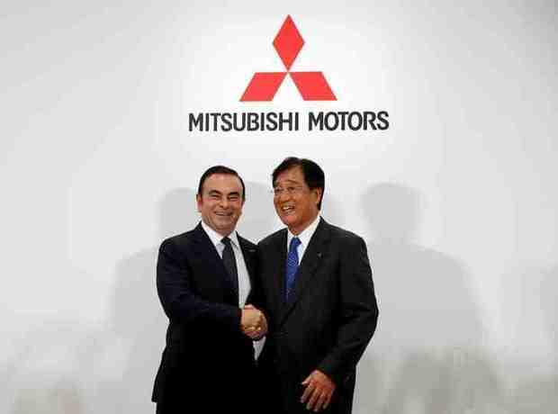 Carlos Ghosn (L), Chairman and CEO of the Renault-Nissan Alliance and Mitsubishi Motors Corp's Chairman and CEO Osamu Masuko attend their joint news conference in Tokyo