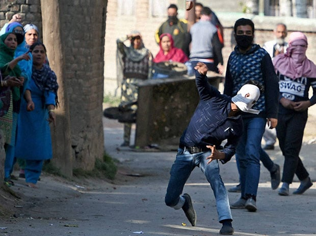 Protesters throw stones at  policemen during a protest in Srinagar. (Photo: PTI)