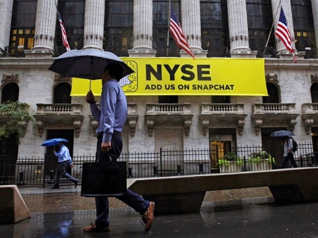 Morning commuters pass by the New York Stock Exchange (NYSE) on a rainy morning in New York City, US.Photo: Reuters
