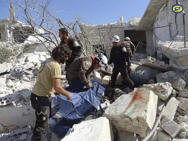 Syrian Civil Defense workers search through the rubble after airstrikes in the village of Hass in the Idlib province, Syria