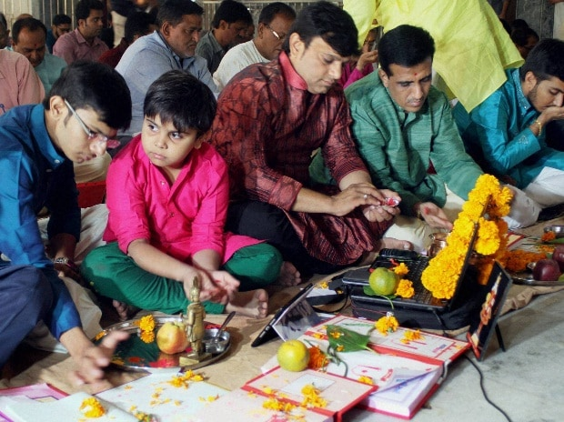 Indian businessmen sit beside their accounts books and electronic gazette  as part of a ritual to worship the Hindu deity of wealth Goddess Lakshmi on Diwali in Ahmedabad.