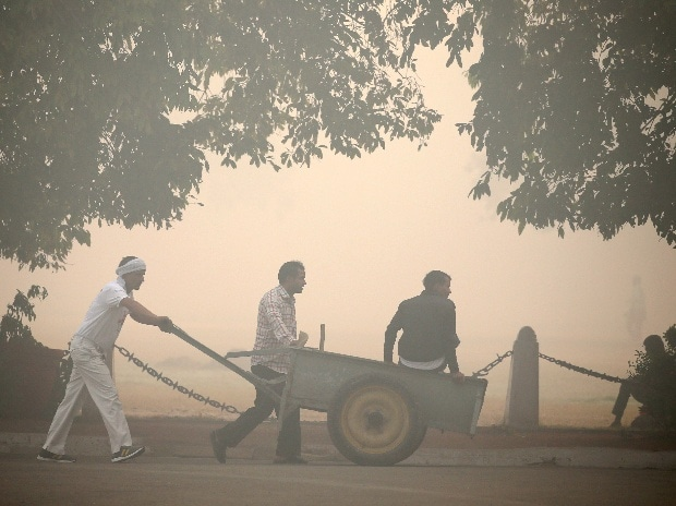 Municipal workers push a cart in a public park on a smoggy morning