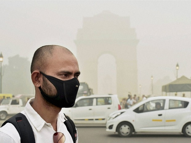 A man takes protection against pollution as smog covers India Gate in New Delhi. (File Photo: PTI)