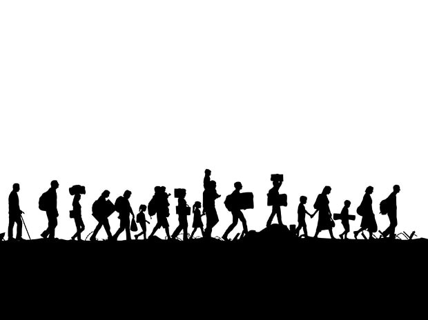 Silhouette of a group of refugees walking through a field. (Photo: Shutterstock)