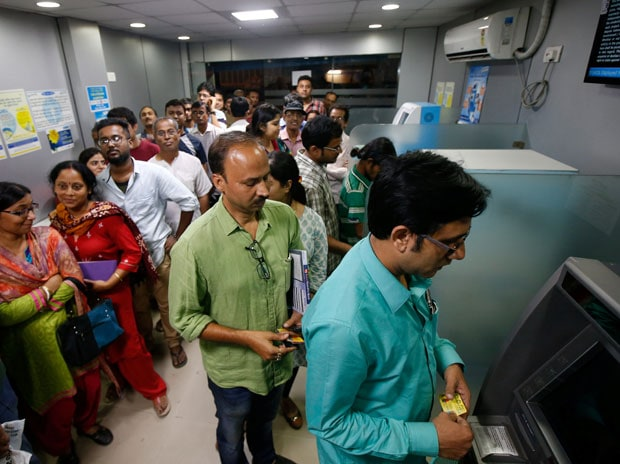People wait to deposit and withdraw their money outside banks and ATMs (Reuters)