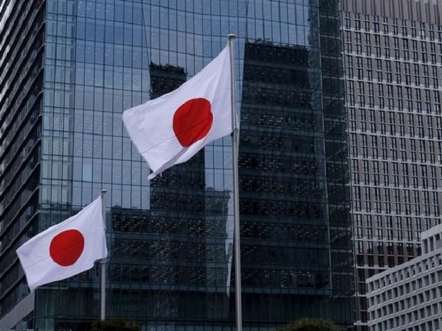 Japanese national flags flutter in front of buildings at Tokyo's business district in Japan.Photo: Reuters