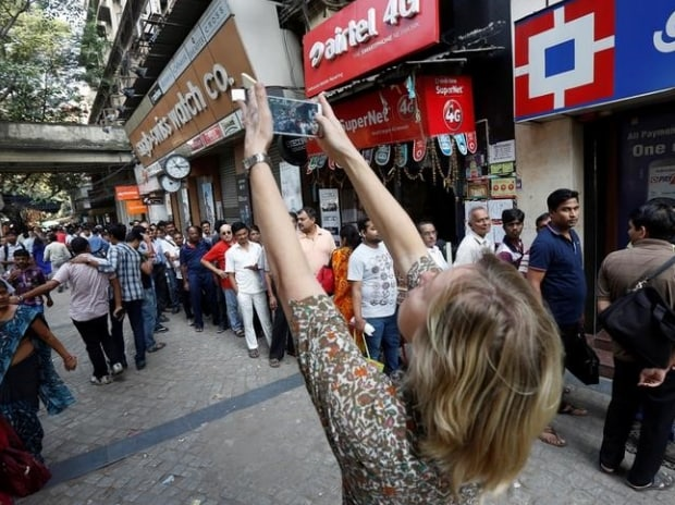 A foreign tourist takes pictures of people standing in a queue outside a bank to exchange and deposit their old, high denomination banknotes in Kolkata