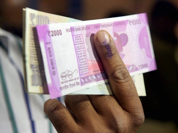 A man shows his inked finger and exchanged currency notes at a SBI branch in New Delhi