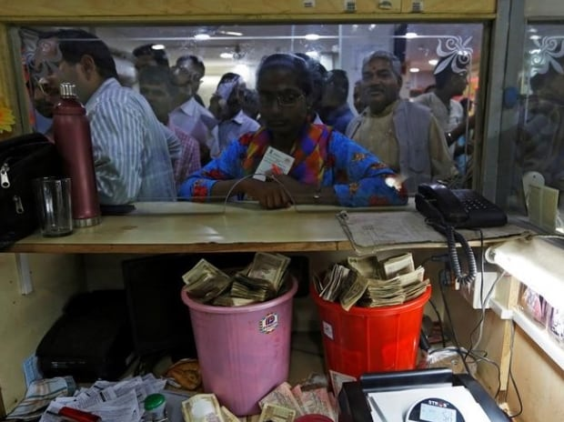 Old high denomination bank notes are seen kept in buckets at a counter as people stand in a queue to deposit their money inside a bank in the northern city of Kanpur