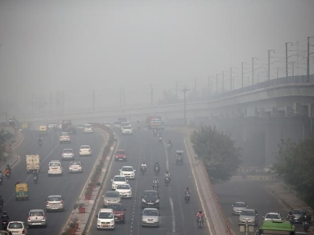 Traffic drives through smog in Delhi