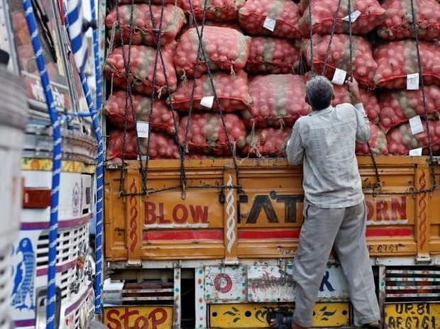 A labourer prepares to unload sacks of potatoes from a truck at a wholesale vegetable and fruit market in New Delhi
