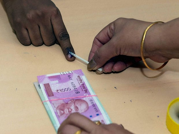 A bank employee applying ink to a customer on exchange of 500 and 1000 rupee currency notes at a SBI branch in New Delhi. (Photo: PTI)